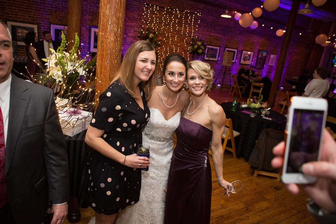 bride poses with two friends for iphone picture